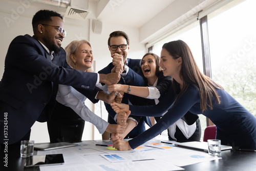 Fotografering Happy laughing businesspeople colleagues of different age and race stacking fist