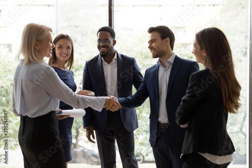 Foto Happy millennial team leader handshaking and greeting warmly senior female execu