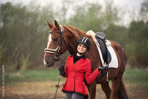 Fotomural Portrait Jockey woman rider with brown horse, concept advertising equestrian clu
