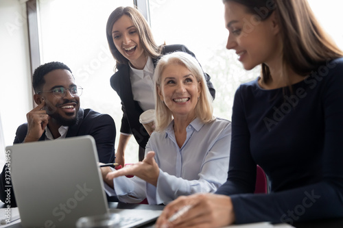 Fototapeta Pleasant mature woman qualified employee explaining business task details to younger colleagues, happy aged lady team leader showing diverse millennial staff solution of problem on computer screen obraz