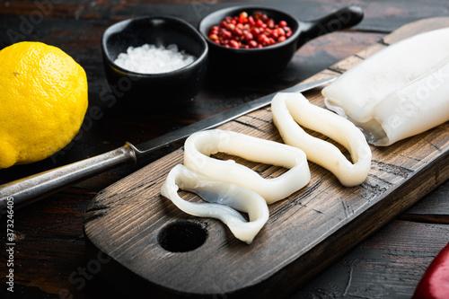 Cuadros en Lienzo Raw squid meat on wooden cutting board on old wooden dark table