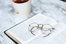 Soft Focus Of An Eyeglass On An Open Bible On A  Table