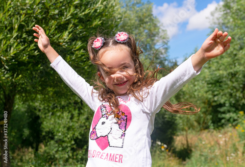 Portrait of a cute beautyful smiling happy little girl with hands up, dancing in a summer park, close-up Wallpaper Mural