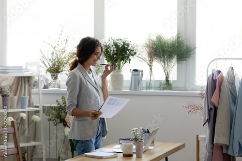 Photo Smiling young businesswoman in glasses holding paper documents with research information, activating voice recognition assistant on mobile phone, recording audio message in social network application