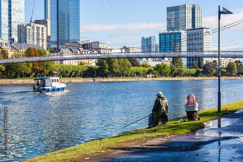 Samotny wedkarz nad rzeka. Relaks na Menem we Frankfurcie. Polow ryb. Panoram miasta w Niemczech.
