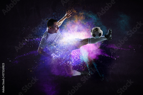 Boy playing soccer hitting the ball Tableau sur Toile