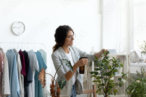 Happy young creative designer in glasses refreshing green leaves of domesticated plants with spray water in modern workplace showroom, beautiful woman taking care of flowers, hobby gardening concept Fototapet