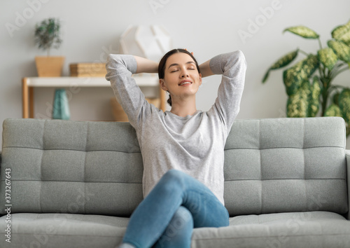 Obraz woman resting on sofa at home - fototapety do salonu