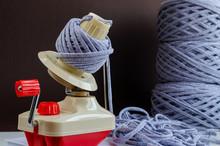 Hand Plastic Wool Winder At Work, Gray Yarn Balls, Brown Background. Prepair For Knitting, Crochet. Handmade Concept
