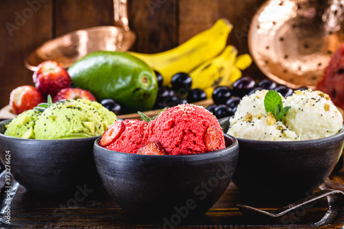 Fotografie, Obraz vegan ice cream made with organic fruits, with tropical fruits in the background