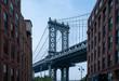 Closeup of Manhattan Bridge between two brown Buildings