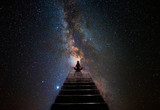 Fototapeta Kosmos - Woman in yoga pose at top of stair
