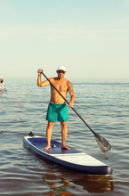 Men Is Training On A SUP Board In The Summer Sea.