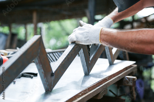 Obraz manual production of metal stairs. hands of a worker are making metal bowstring for stairs in a workshop close up outdoor - fototapety do salonu