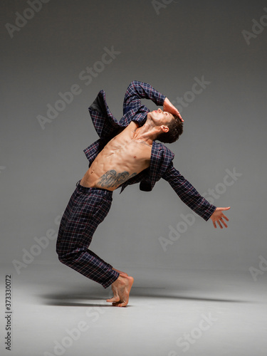 Fotografia Handsome young guy dancer in suit and barefoot dancing expressive dance