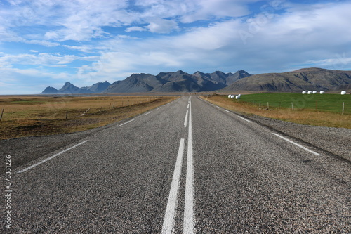 Slika na platnu Straight road with white stripes, mountains, pasture and blue sky with clouds in