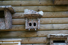 Closeup Shot Of A Stone Birdhouse On A Wooden Wall