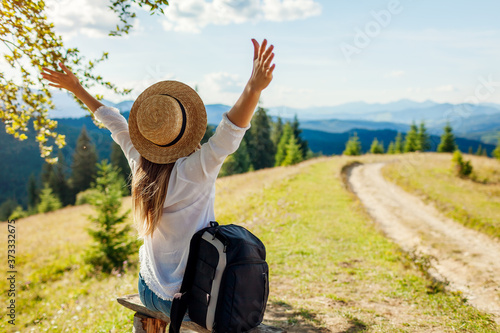 Trip to Carpathian mountains. Woman hiker relaxing admiring landscape with arms raised. Traveling in summer Ukraine