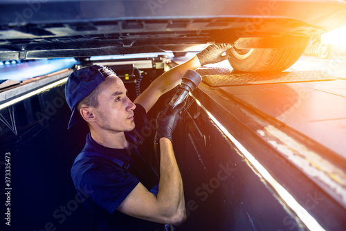 Leinwand Poster Car mechanic examining car suspension of lifted automobile at service station