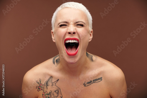 Tela Female with short blond hair, red lipstick on lips and tattoos on chest and neck