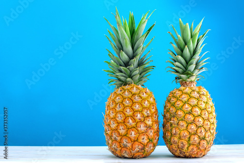 Fotografia two fresh ripe pineapples on blue background
