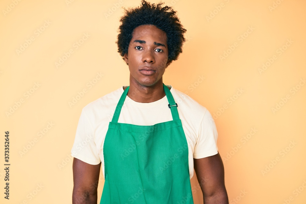 Fototapeta Handsome african american man with afro hair wearing waiter apron with serious expression on face. simple and natural looking at the camera.