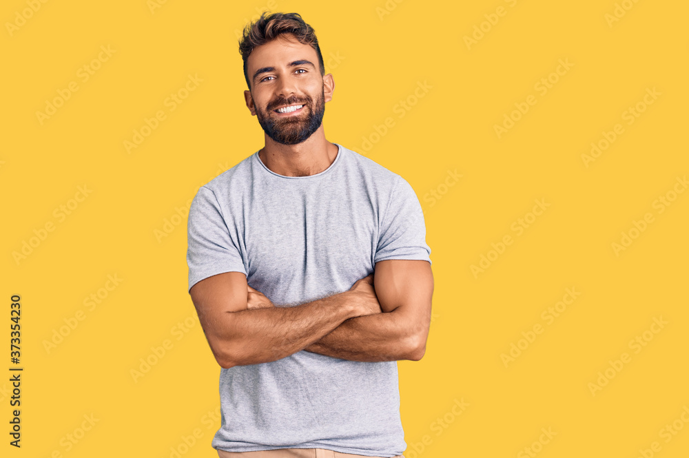 Fototapeta Young hispanic man wearing casual clothes happy face smiling with crossed arms looking at the camera. positive person.