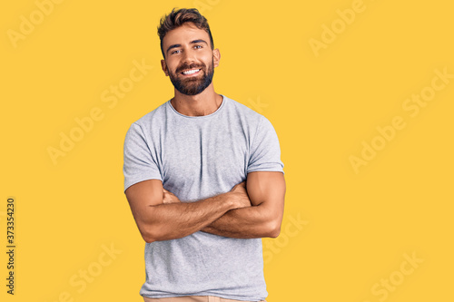 Obraz Young hispanic man wearing casual clothes happy face smiling with crossed arms looking at the camera. positive person. - fototapety do salonu