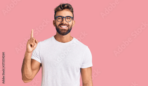 Obraz Young hispanic man wearing casual clothes and glasses showing and pointing up with finger number one while smiling confident and happy. - fototapety do salonu