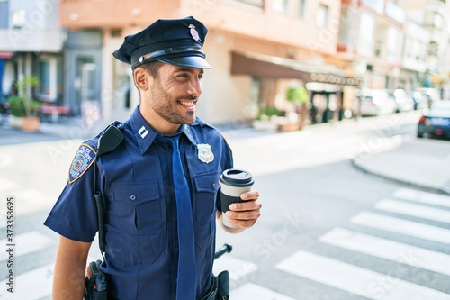 Foto Young hispanic policeman wearing police uniform smiling happy
