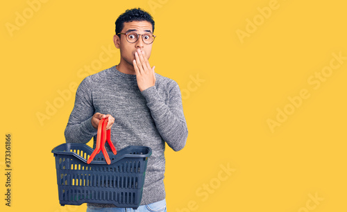 Fotografija Hispanic handsome young man holding supermarket shopping basket covering mouth with hand, shocked and afraid for mistake