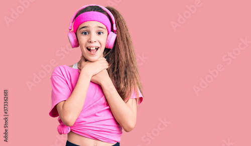 Photo Cute hispanic child girl wearing gym clothes and using headphones shouting and suffocate because painful strangle