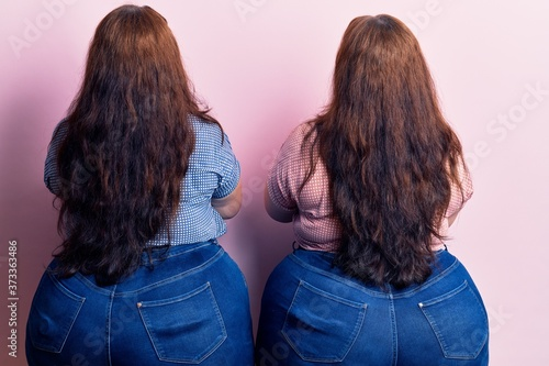 Fotografia Young plus size twins wearing casual clothes standing backwards looking away wit