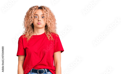 Obraz na plátně Young blonde woman with curly hair wearing casual red tshirt puffing cheeks with funny face