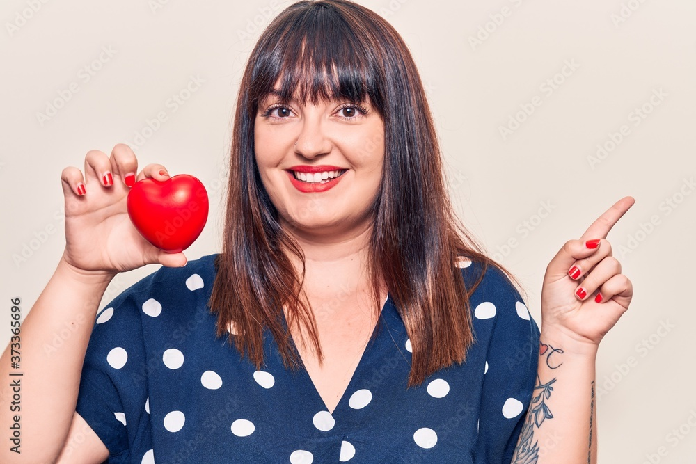 Fototapeta Young plus size woman holding heart smiling happy pointing with hand and finger to the side