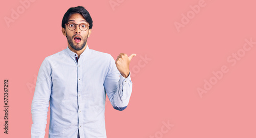 Fotografía Handsome hispanic man wearing business shirt and glasses surprised pointing with hand finger to the side, open mouth amazed expression