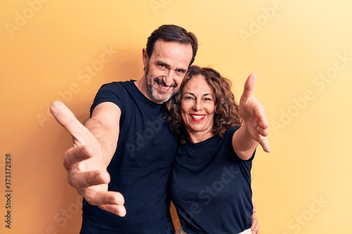 Obraz na plátně Middle age beautiful couple wearing t-shirt standing over isolated yellow background looking at the camera smiling with open arms for hug