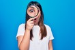 Young beautiful brunette woman using magnifying glass over isolated blue background scared and amazed with open mouth for surprise, disbelief face