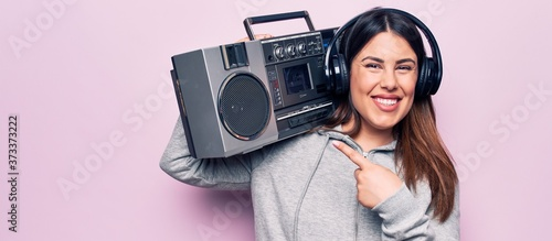 Obraz Young beautiful brunette woman listening to music using vintage boombox and headphones smiling happy pointing with hand and finger - fototapety do salonu