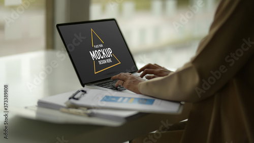 Female typing on mock up laptop while working with document files on worktable Canvas Print
