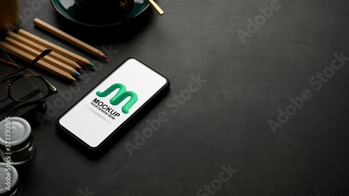 Photo Cropped shot of mock up smartphone on black leather worktable