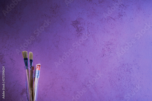 Paint brushes on the background of a decoratively painted wall Fototapet