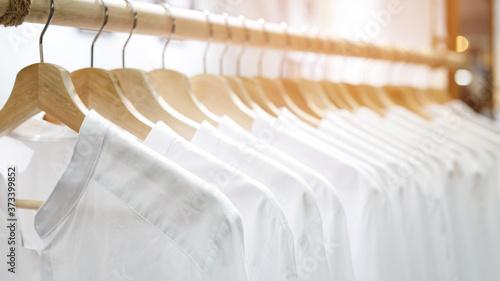 Fototapeta Female clothes shirts white on rail hanging on hangers.