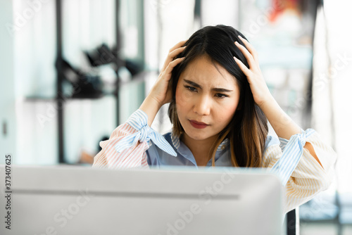 Young Asian woman with computer problems in the office. Slika na platnu