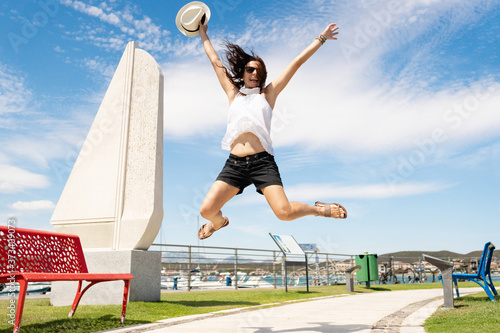 Vászonkép Young caucasian happy woman jump in the air with open arms - Low angle view of a