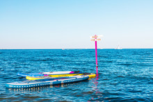 Surfing Boards Are Tied To A Wooden Post In The Sea. Hire And Rent Of Stort Accessories For Swimming. Summer And Active Extreme Vacation Concept