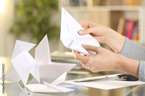 Woman hands doing origami figures at home Canvas Print
