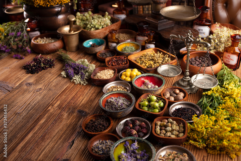 Fototapeta Natural medicine background. Assorted dry herbs in bowls and brass mortar on rustic wooden table.
