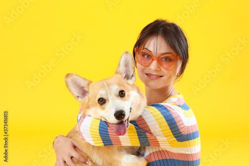 Woman with cute corgi dog on color background Billede på lærred