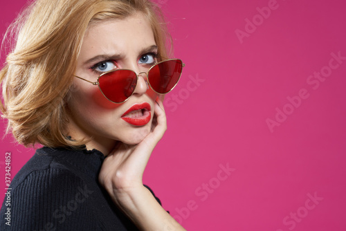 Cuadros en Lienzo Pretty woman in dark glasses bright makeup black jacket close-up pink background
